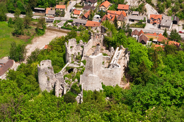 Medieval castle ruins in green forest. Aerial view.