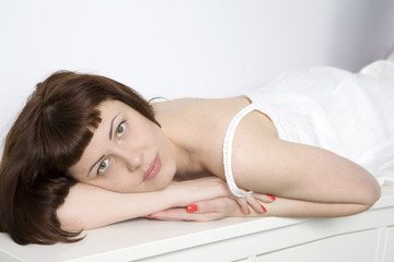 Portrait of a beautiful young woman relaxing on bed