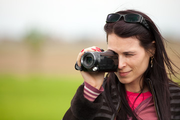 Young lady using video camera outdoors
