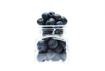 blueberries in a glass bottle isolated on white