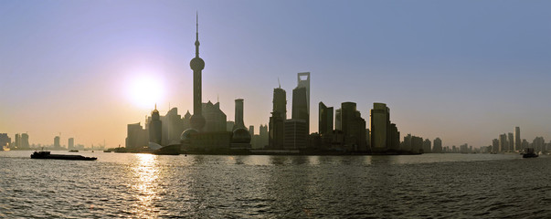The sun rises behind the skyline of Shanghai's Pudong district