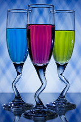 Blue, pink, and green liqueur in curved glasses