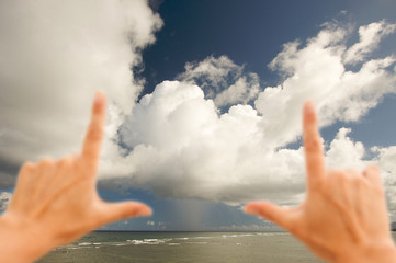 Hands Framing Dramatic Clouds over Tropical Shoreline