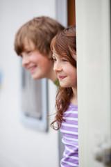 zwei kinder schauen aus dem wohnwagen