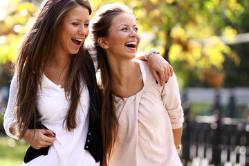 Two cheerful girls twins, in the street