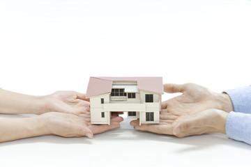 住宅模型を手に乗せる夫婦