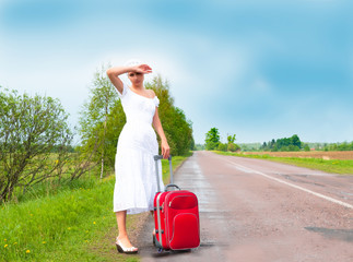 girl in white dress with suitcase on road