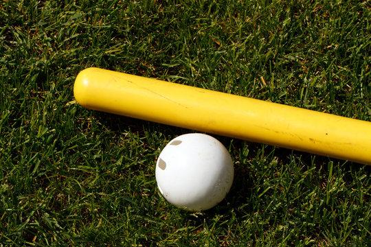 Yellow plastic bat and white whiffle ball