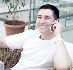 Smiling young man working on laptop computer and call by phone a
