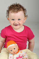 Baby girl with her doll on grey background looking at camera