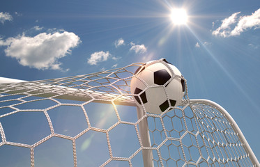 Soccer ball in the net on the sky background