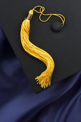 Black mortarboard, blue gown, yellow tassel