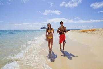 beachboy plays his ukulele for a girl as they walk on a beach