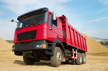 red dumper truck transportation of construction sand