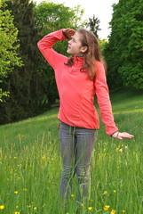 Ein Teenager steht auf der Wiese und schaut in die Weite.
