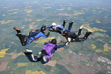 Four skydivers in freefall holding hands