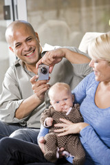 Parents with baby at home, dad holding camera