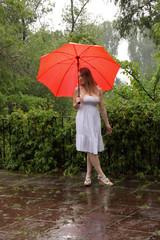 Frau im Sommerkleid unter Regenschirm