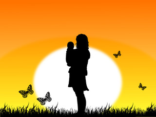 Silhouettes of a woman and a baby on sunset