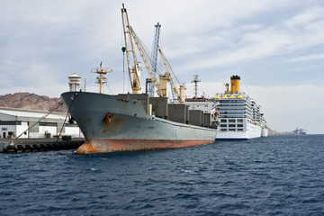 The cargo ship with its own cranes is docked at a shipyards.