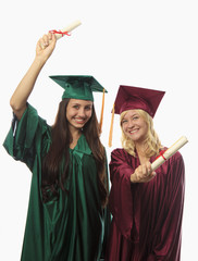 two female college graduates in cap and gown.
