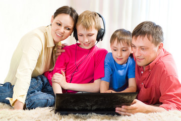 family lying on the carpet with a laptop