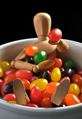 Wooden doll in a bowl of jelly beans