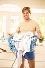 Smiling guy with laundry basket