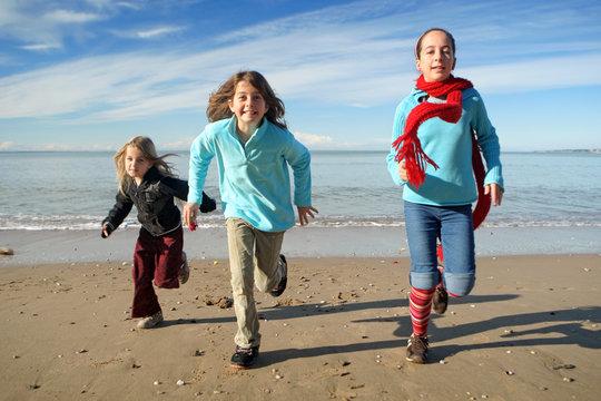 Trois enfants courant sur la plage