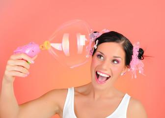 Beautiful happy teenage girl blowing soap bubbles and having fun