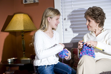 Girl with grandmother knitting at home