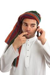Pondering arab businessman using phone