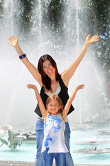 Mother and daughter holding their arms in the air with delight