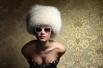 Sexy womanб white fur hat, golden vintage floral background.