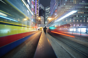 Fotobehang - Fast moving bus lights blurred over modern city background