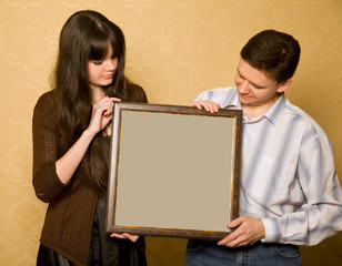 young beautiful woman and smiling man with picture in frame