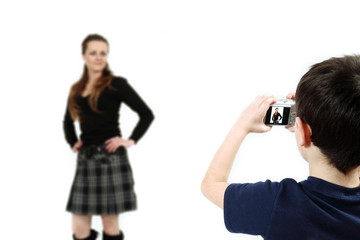 Young boy with digital camera shooting girl