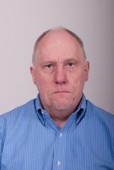 Older Balding Man in Blue Shirt Looking Unhappy