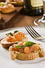 Bruchettas de tomate marinado, queijo ralado e manjericão