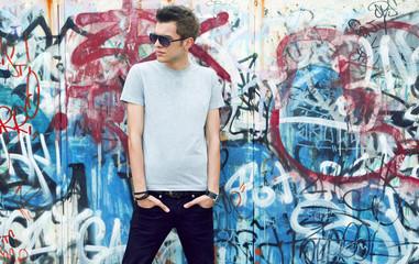 In de dag Graffiti young man posing in front of a colorful graffiti wall