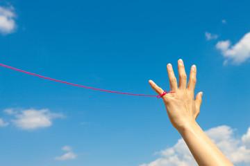 青空と女性の小指に赤い糸