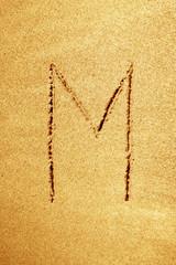 Alphabet letter handwritten in sand on a beautiful beach