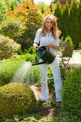 Frau mit Blumen im Garten mit Gießkanne