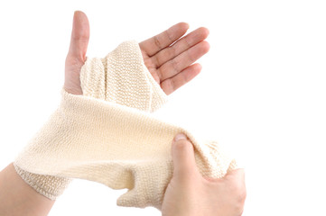 Woman wrapping her hand with a bandage on a white background