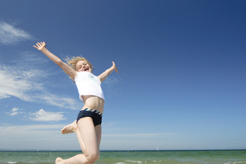 Jumping girl on the beach. Happiness concept
