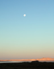 Moon rising over a lagoon in the late afternoon