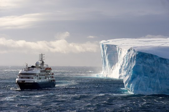 The cruise ship Corinthian II in front of a huge Iceberg