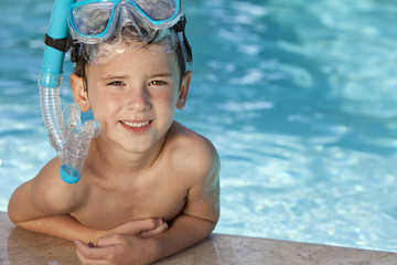 Happy Boy In Swimming Pool With Blue Goggles and Snorkel