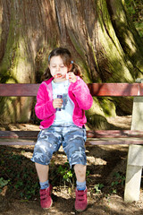 A girl blowing soap bubbles in a natural outdoor setting.