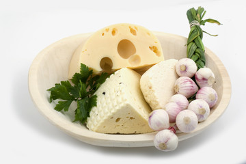 Wooden plate with cheese and garlic isolated
